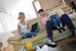 bigstock-happy-young-family-using-table-57002552